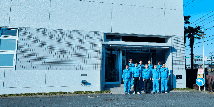 Group photo of President Keiichi Nishihara and employees in front of the factory